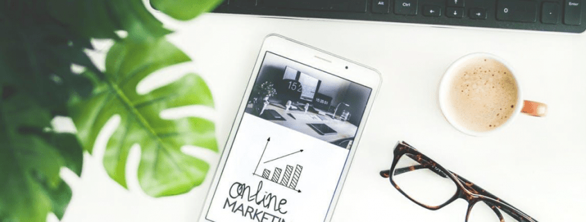 view od desk with mobile phone showing online marketing on screen