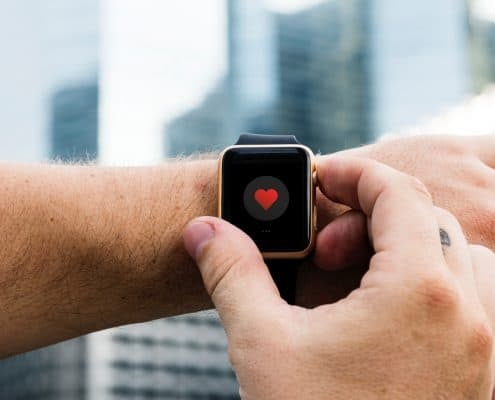apple watch user showing heart icon on watch